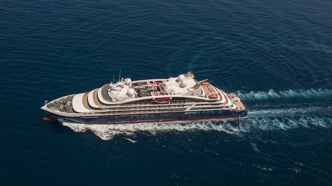 Aerial view of Le Jacques Cartier luxury expedition ship cruising in open waters, with dark blue & red hull & white upper decks.