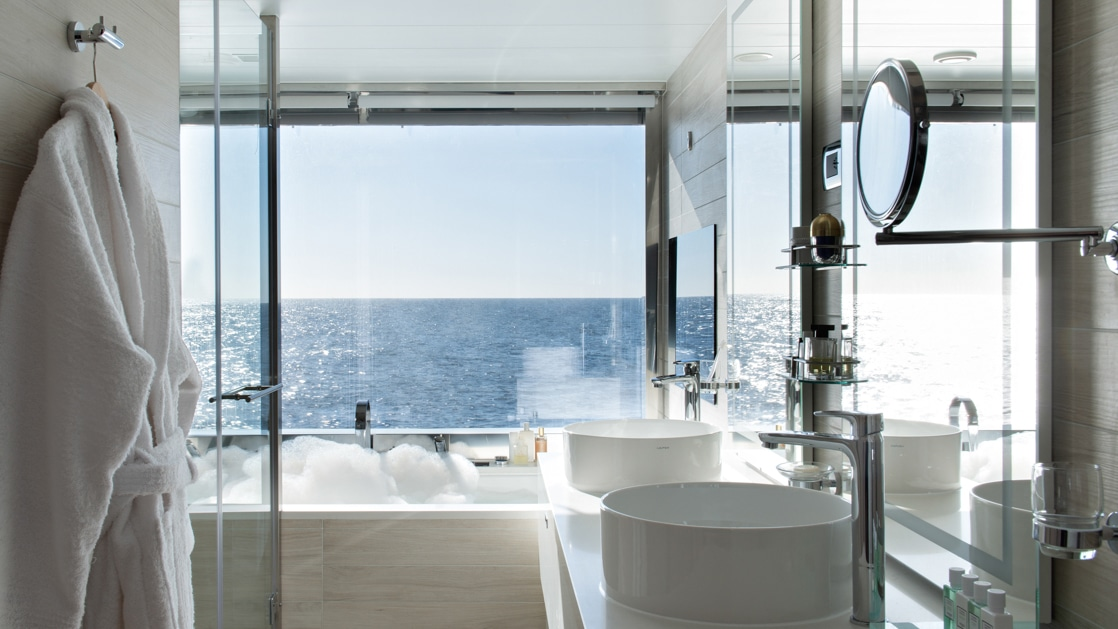 Floor-to-ceiling window beside a large white bathtub with a white robe hanging beside the vanity on Le Jacques Cartier French ship.