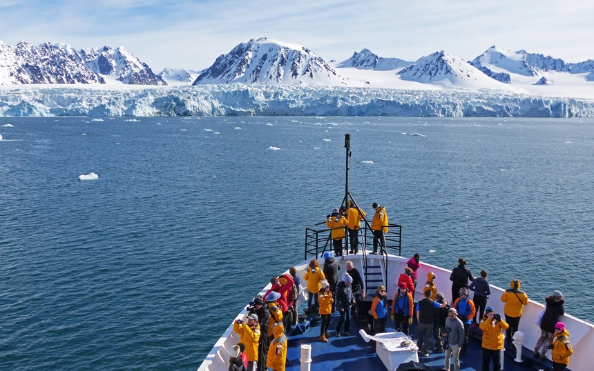 Arctic cruise passengers gather at the bow of the ship to take in the views of the sprawling massive ice shelf in Svalbard.
