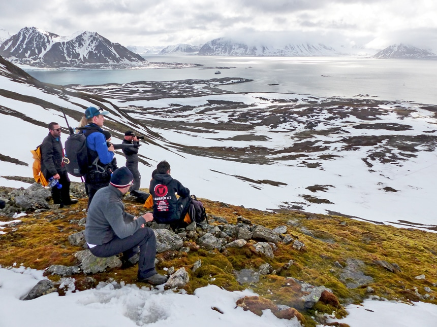 A group hiked to a view point during a shore excursion of their Arctic Svalbard cruise, they look out over the snowy landscape below them.