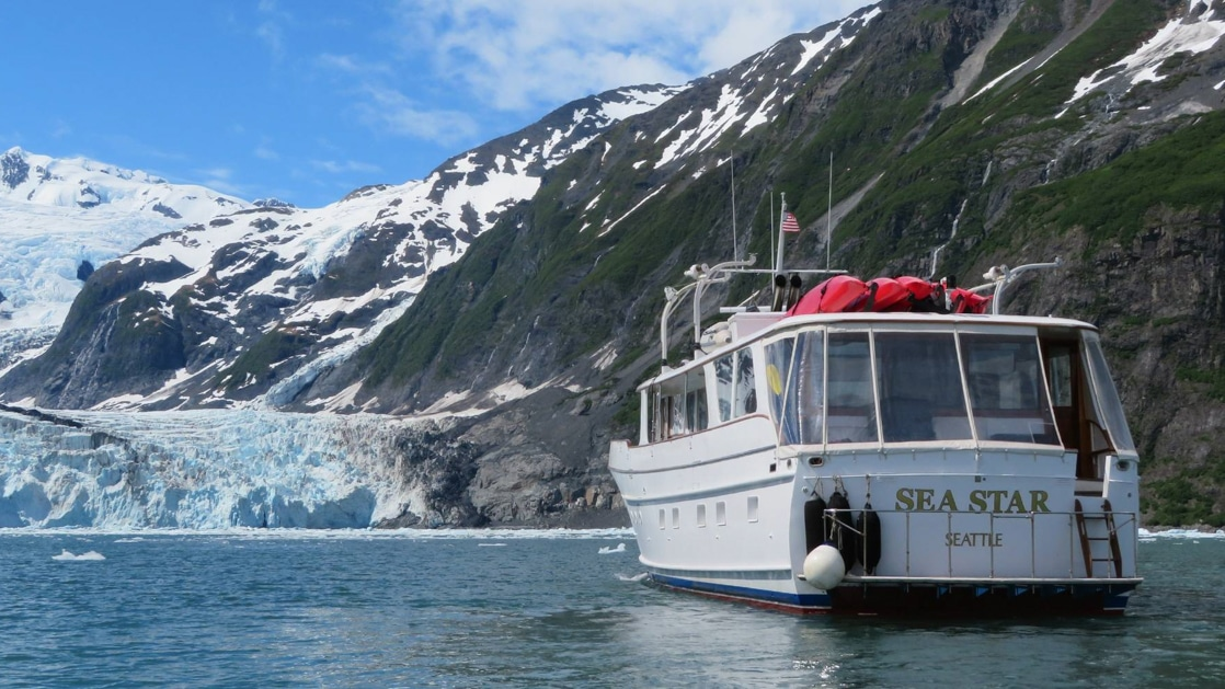 Yacht with white exterior & 3 red kayaks on top sits and looks toward a large blue glacier during the Alaska Explorer: Kenai Peninsula & Prince William Sound tour.