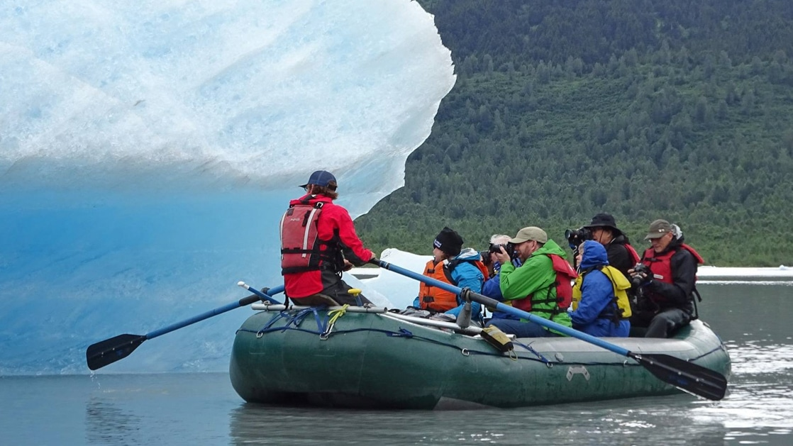 Group of Southcentral Alaska travelers photograph a large iceberg as their tour leader paddles them beside it during the Alaska Explorer trip.