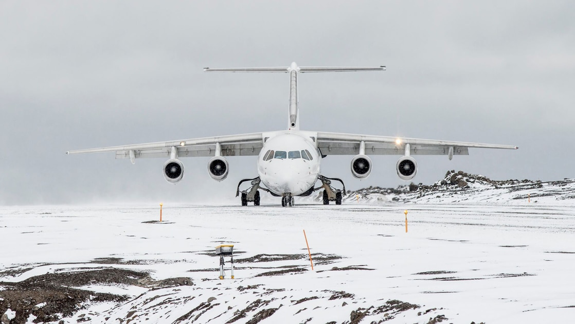A white snowy landscape on a overcast day, a white charter plane sits on an empty runway ready for Antarctica Air cruises.