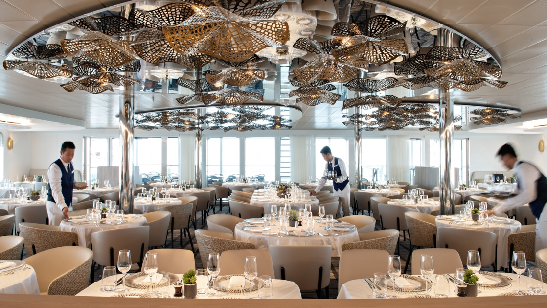 Dining room with elegant white tablecloths & floral gold light fixtures, being set for dinner by servers aboard Le Bellot Ponant ship.