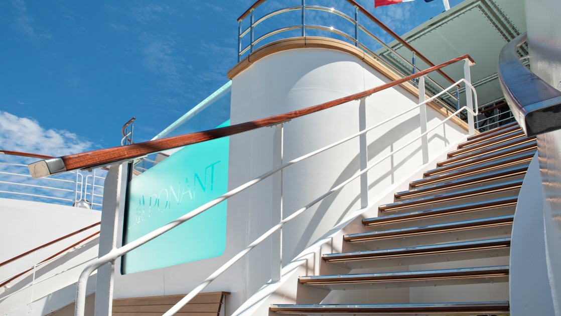Teak wood staircase leads up to the edge of a turquoise infinity pool aboard Le Bellot French ship.