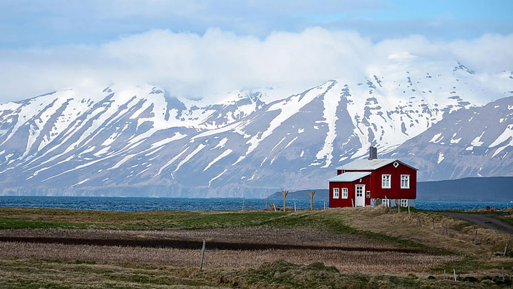 Small red house sits on stilts overlooking blue water with snowcapped peaks in the background, seen on an Iceland cruise.
