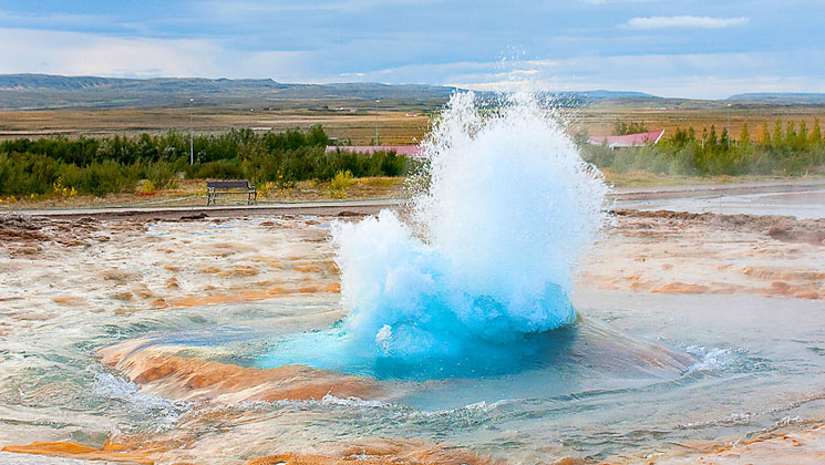 Geothermal pool explodes with icy-blue hot water amidst tangerine sand & sediment in Iceland.