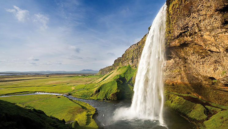 Large waterfall cascades into a small pool amidst bright green fields in Iceland.