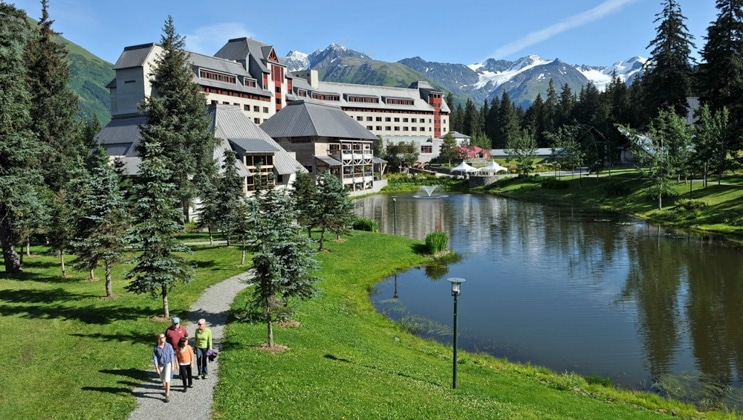 Aerial view of Hotel Alyeska, a chateau-style, multi-story gray hotel set among lush grass, a pond & mountains, on a sunny day.