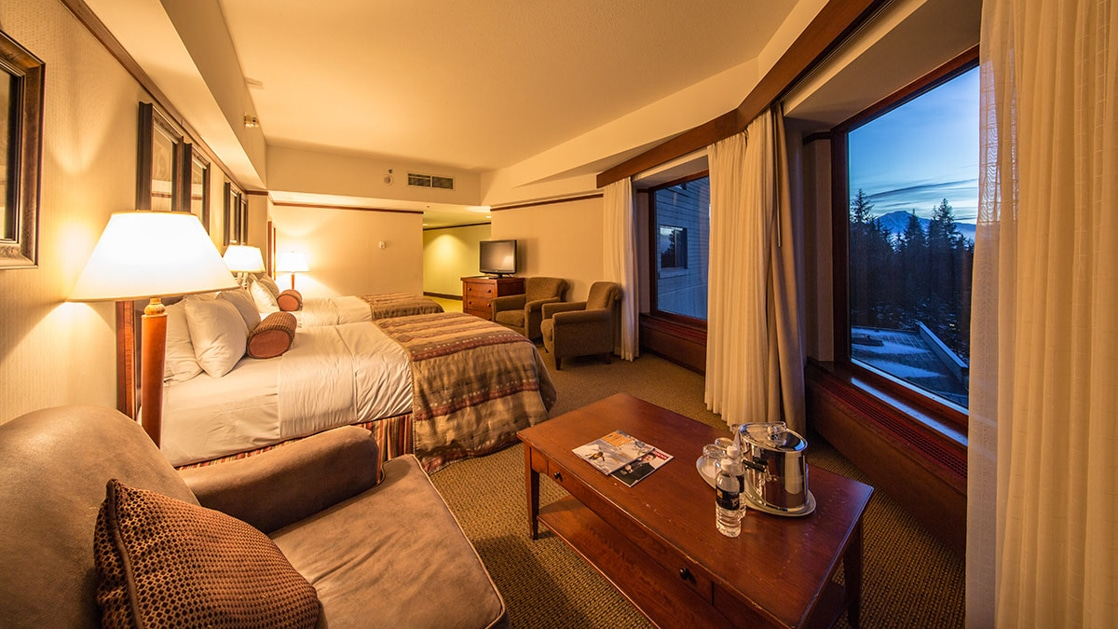 Hotel Alyeska Junior Suite with 2 double beds, padded chairs, TV, wooden coffee table & dresser, beige & tan accents & wraparound windows.