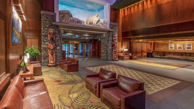 Lobby of Hotel Alyeska, with leather chairs & sofas, wooden walls, totem poles & stuffed bear, plus soft lighting & large entryway.