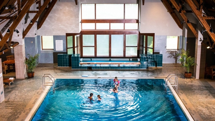 Family swims in large indoor pool with turquoise-colored water, with large Jacuzzi behind, at Hotel Alyeska near Girdwood, Alaska.