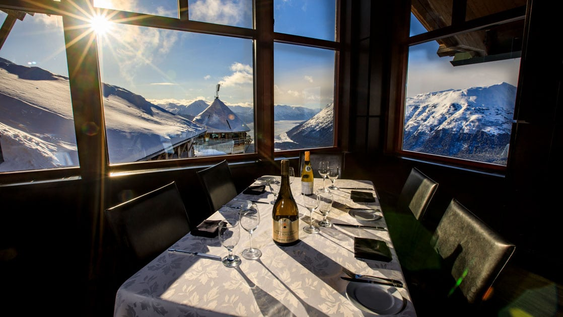 Table set for 4 with white tablecloth, classy dinnerware & panoramic view overlooking snowy mountains & lake below, at Hotel Alyeska.