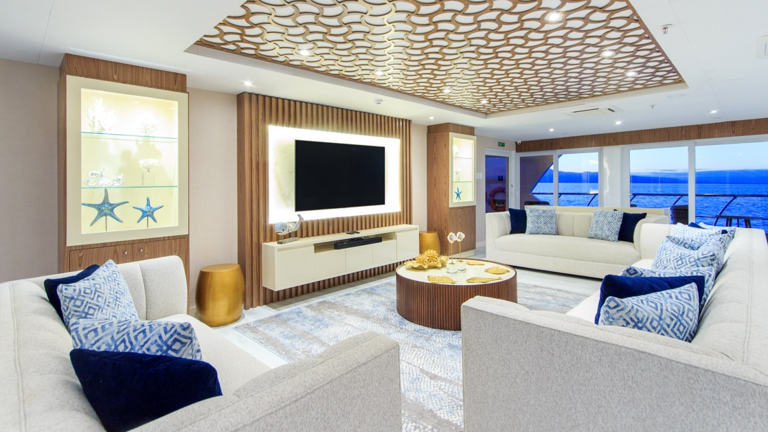 Living room on mc Elite Galapagos ship, with white couches circling a flatscreen TV & small round coffee table, with view windows behind.