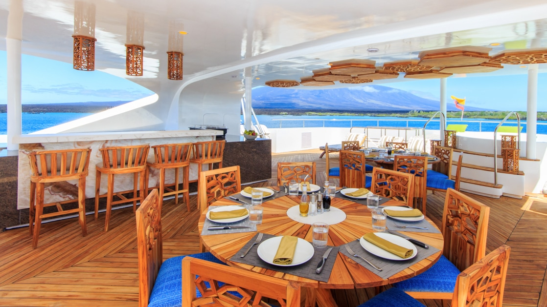 Al fresco dining area set for a meal on Elite catamaran in Galapagos, with teak furniture, marble bar, Jacuzzi & wooden accents.