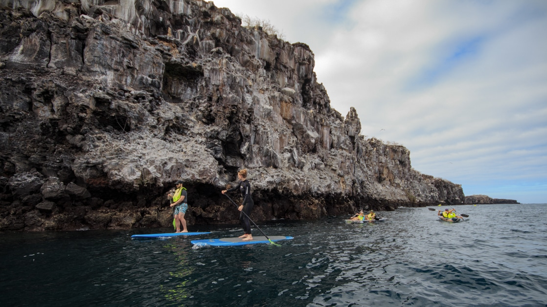 2 stand-up paddleboarders & 2 kayakers paddle beside tall gray cliffs on a partly cloudy day during an Elite Galapagos cruise.