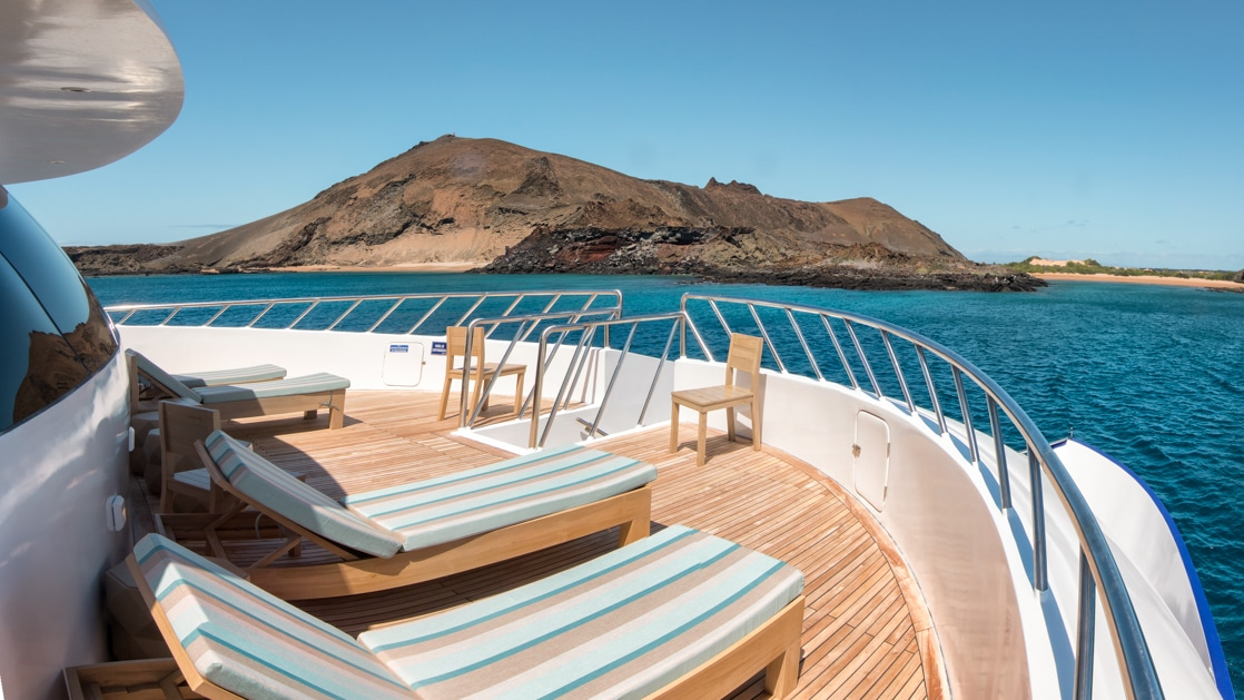 View forward from padded teal sun loungers on teak deck of M/C Endemic Galapagos cruise ship, on a sunny day.