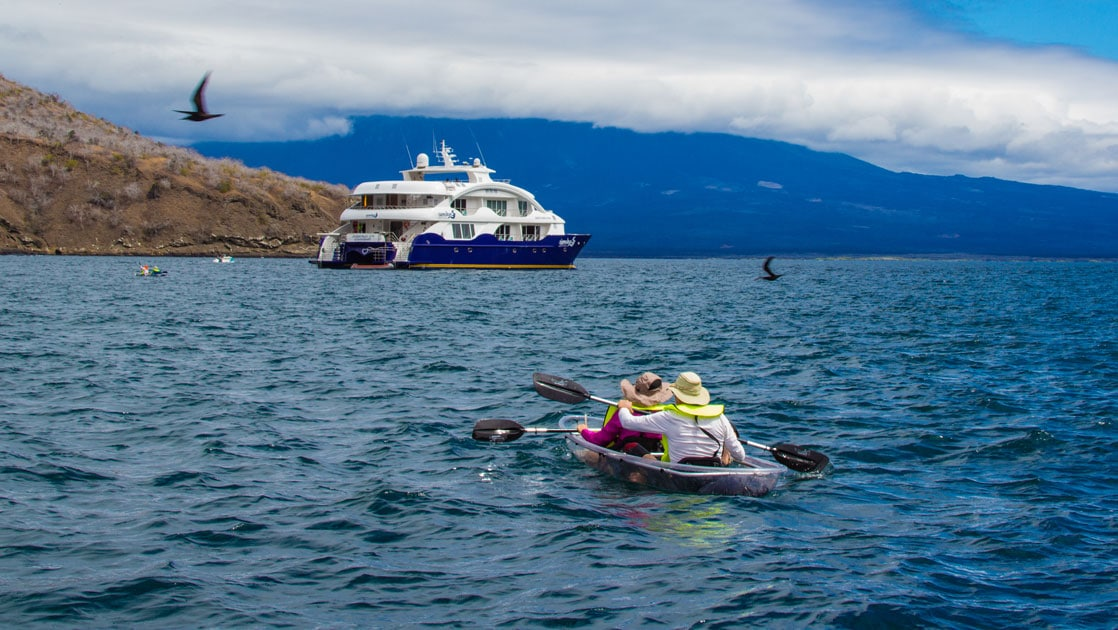 Tandem kayakers in bright yellow PFDs paddle calm water toward a blue & white catamaran with birds overhead on a sunny day in the Galapagos.