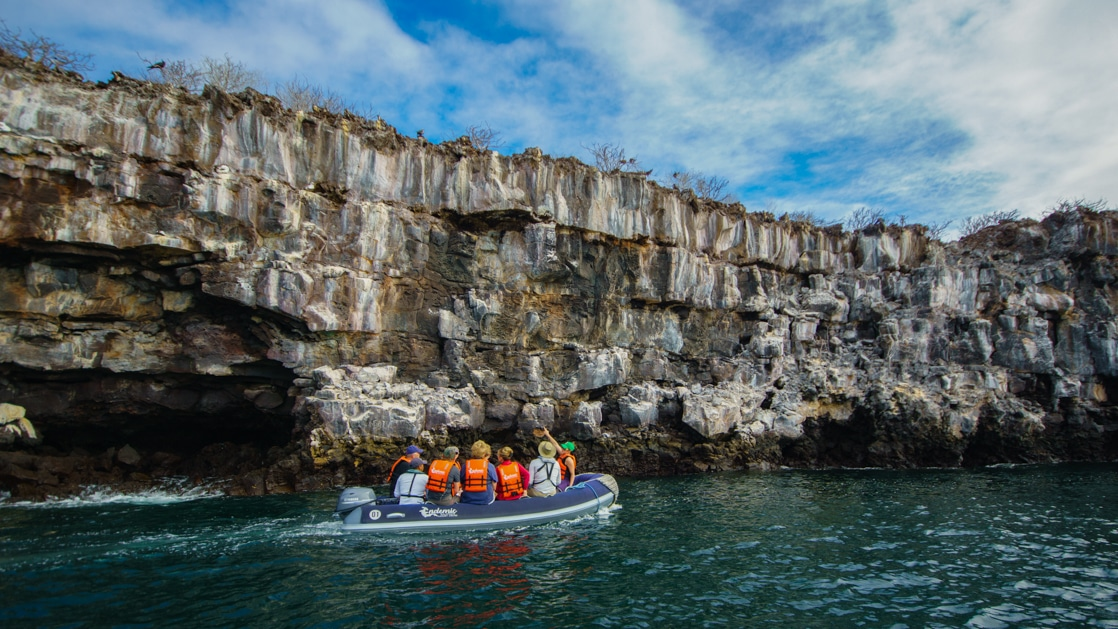 Endemic Galapagos catamaran travelers in orange PFDs ride in a Zodiac through calm water along a rocky cliff on a sunny day.