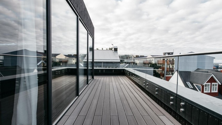 Long wraparound deck with glass railing beside walls of glass in slate gray under a cloudy sky at the Exeter Hotel in Reykjavik, Iceland.