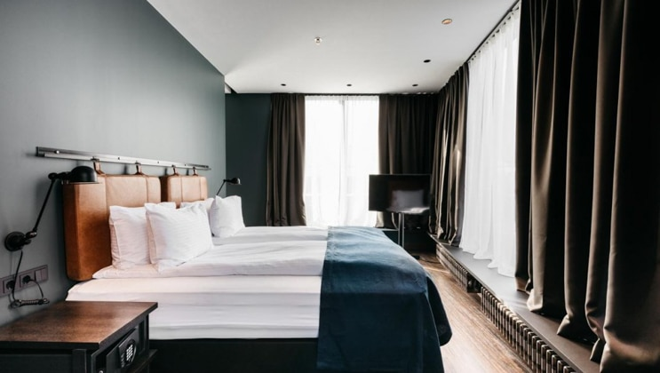 Exeter Hotel room with double bed with white & dark blue linens & tan pads hanging as headboard, wood floors & wraparound walls of windows.