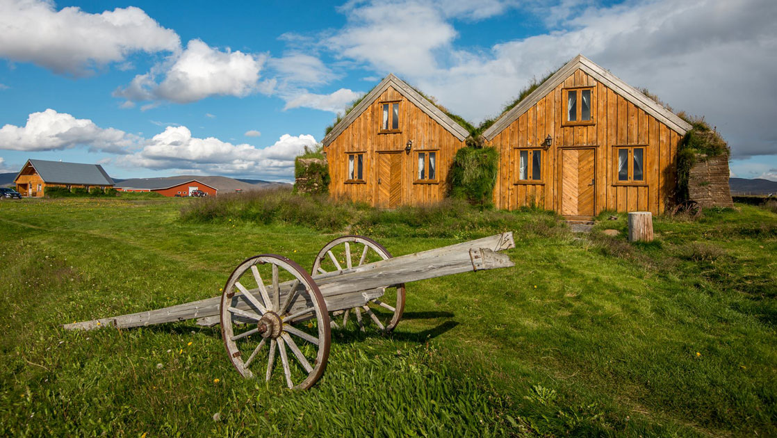 Wooden guesthouses with sod roofs in a grassy field with old farm equipment in front, on a sunny day at Fjalladyrd Guesthouse in Iceland.