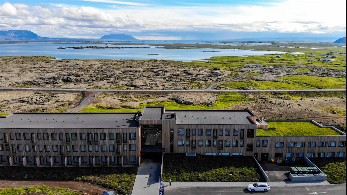 Aerial view of Fosshotel Myvatn Iceland hotel. A modern wood-paneled building sitting on a hillside overlooking the iconic lake.