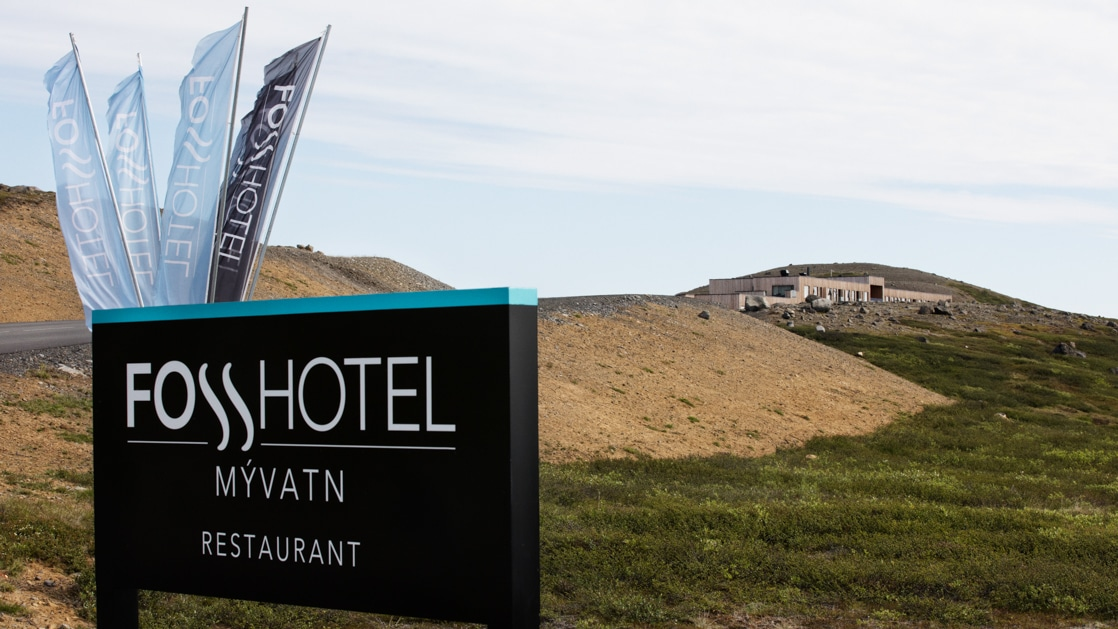 Outdoor hotel sign in dark brown with flags rising behind, advertises the Fosshotel Myvatn, with building in background & green hills in front.