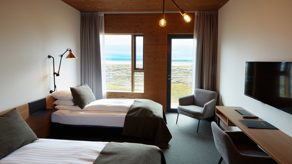 Guest room at Fosshotel Myvatn, with white & wood walls, twin beds with white & green linens, flactscreen TV, wooden desk & lake views.