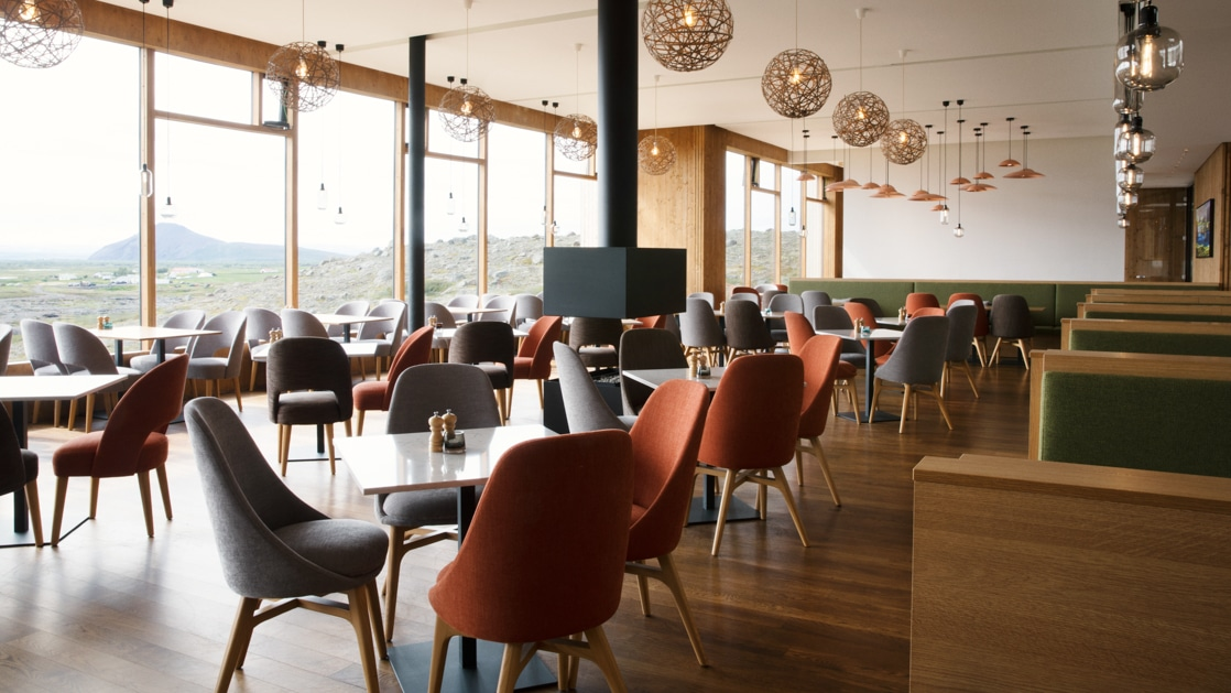 Restaurant at Fosshotel Myvatn, with hanging globe lights, Scandinavian furnirture & wall-to-ceiling windows overlooking the lake.
