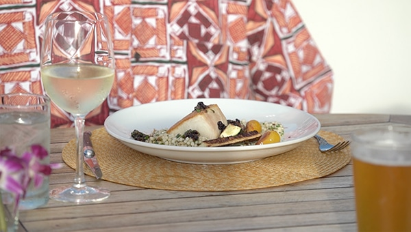 Seared ono fish on a plate with white wine and a Hawaiian Island shirt in the background
