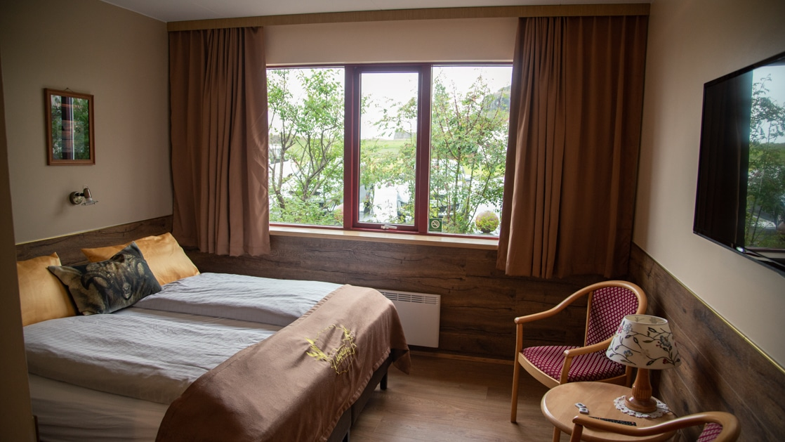 Hotel room with double bed, 2 padded wooden chairs & small wood coffee table, flat screen TV, large window & beige & gold accents.