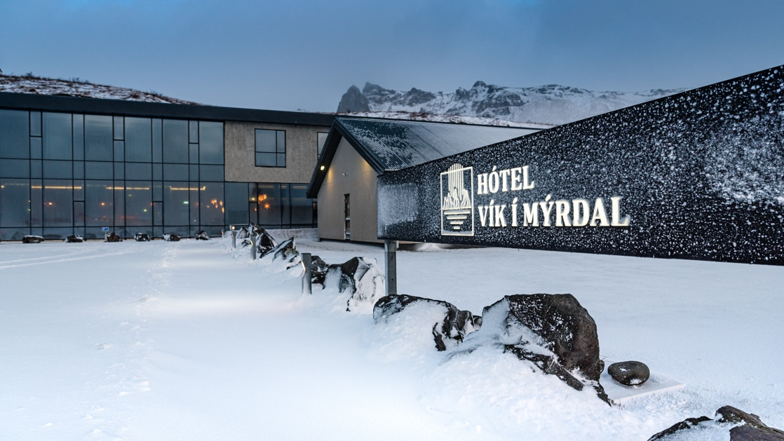 Exterior ground-level view of Iceland Hotel Vik i Myrdal in winter at dusk, with glass walls & illuminated black rectangular sign.