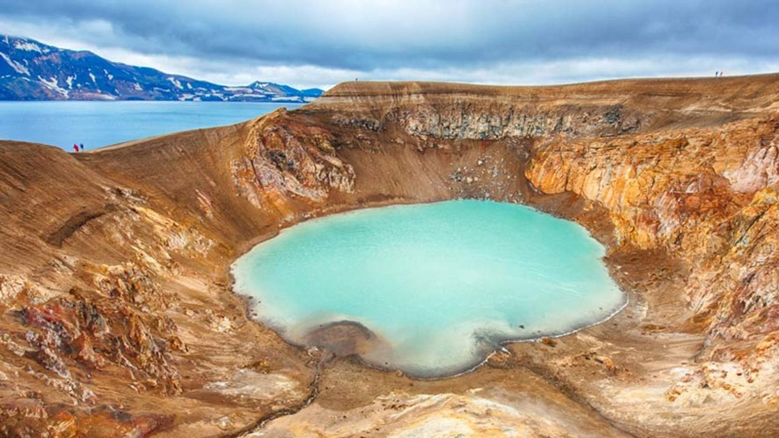 Aerial view of large tan volcanic crater with milky turquoise water in the center, seen on the Iceland Adventure: Land of Fire & Ice tour.