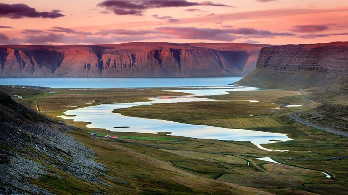 Aerial view of glacier-carved canyon at sunset, with green hillsides, purple mesas and large blue river, seen on the Iceland Adventure tour.