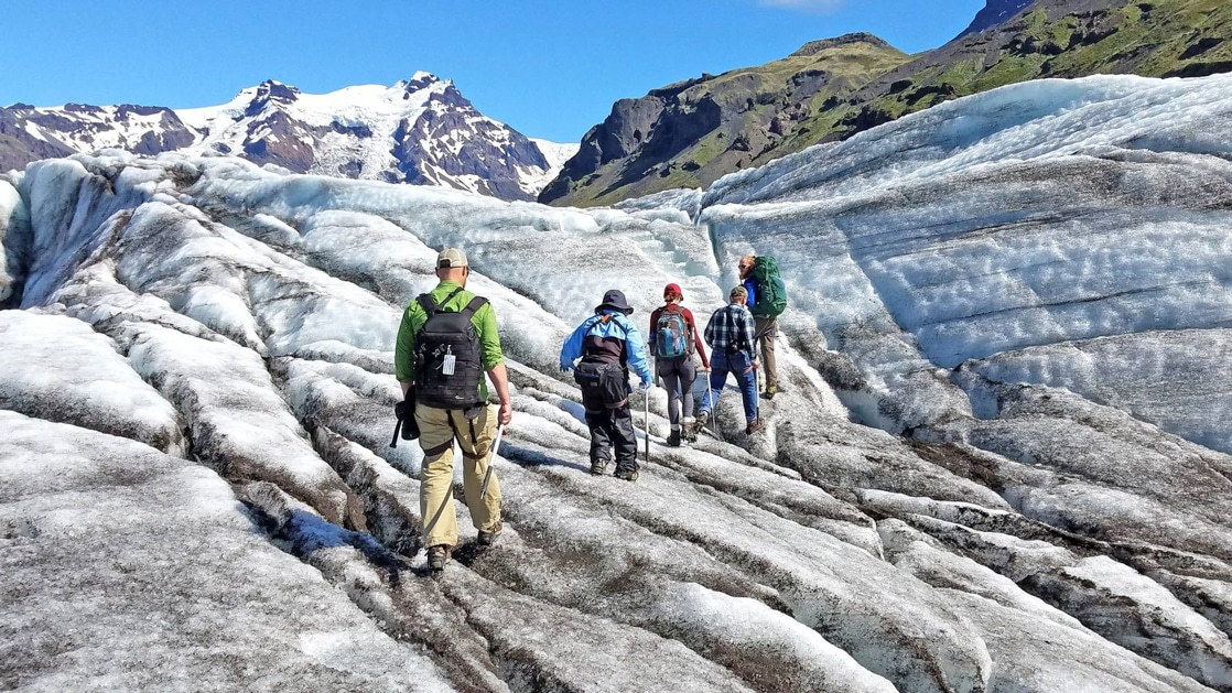 Travelers trek atop a dirty white & blue glacier on a sunny day during the Iceland Adventure: Land of Fire & Ice tour.