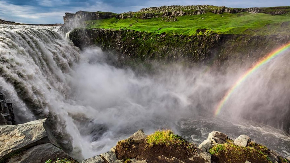 Huge waterfall sends rushing water down past lush green hillsides, with spray from the water creating a rainbow on the Iceland Adventure.