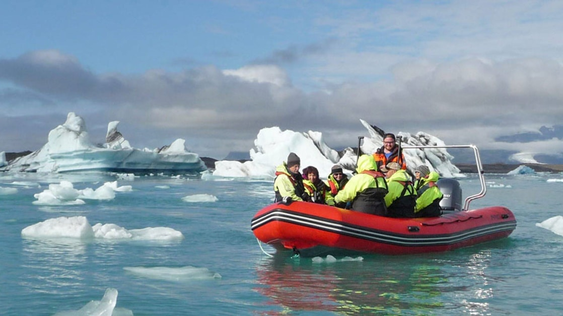 Group of Iceland Adventure travelers in dayglo green jackets Zodiac cruise among icebergs in calm water during a partly cloudy day.