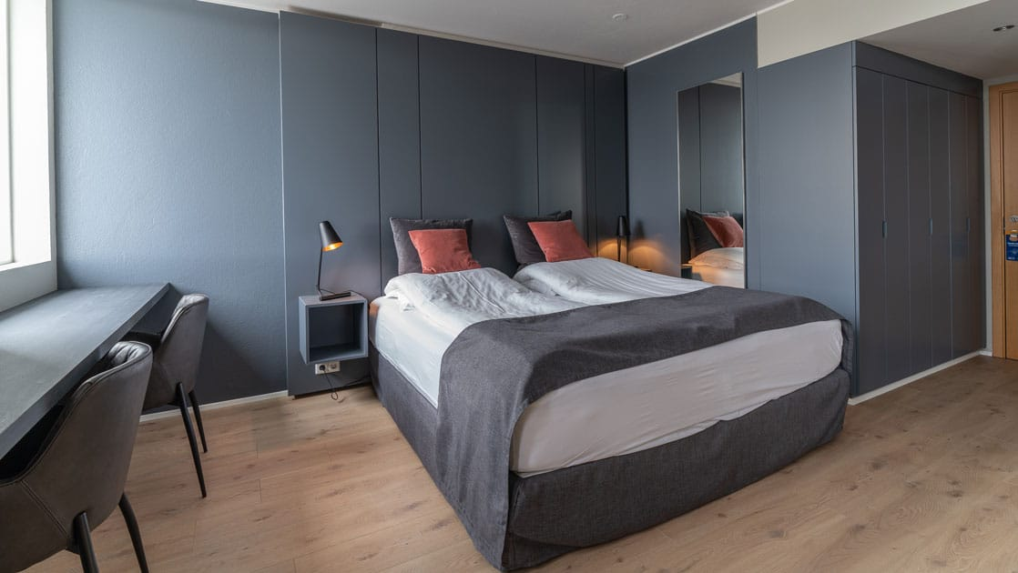 Double bed with white & gray linens in modern hotel room with gray walls & wooden floors at Hotel Isafjordur in Iceland.