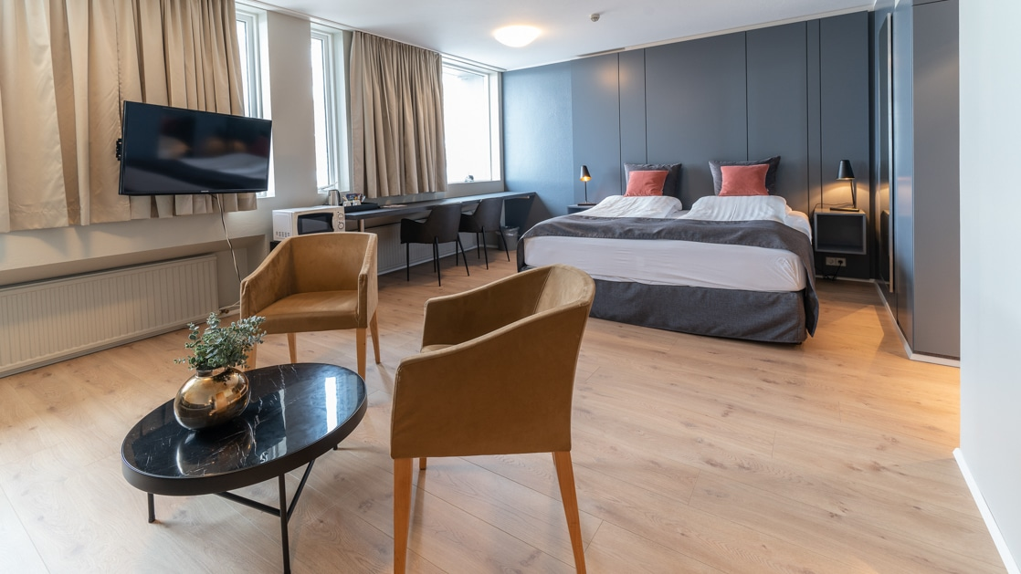 Double bed in modern hotel room with view windows, flat screen TV & seating area with 2 padded tan chairs & small black coffee table.