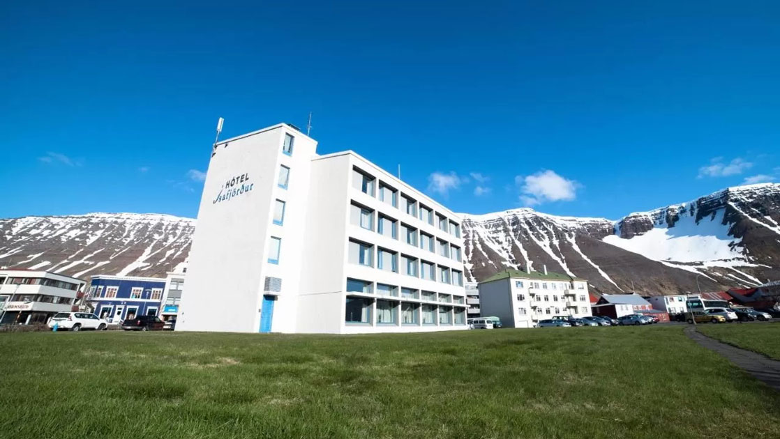 Exterior view of Iceland Hotel Isafjordur, a 4-story white building in the center of town, with green grass & mountains behind.