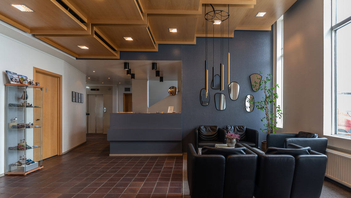 Lobby of Iceland Hotel Isafjordur, with wood floors, glass bookshelf with handicrafts, recessed lighting in cascading wood boxes, & black leather couches.