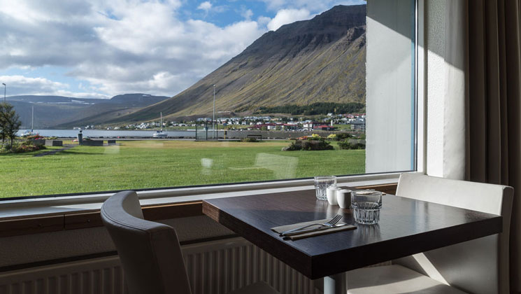 View out window from 2-top table with padded chairs in Iceland Hotel Isafjordur restaurant, looking at fjord & green grass.