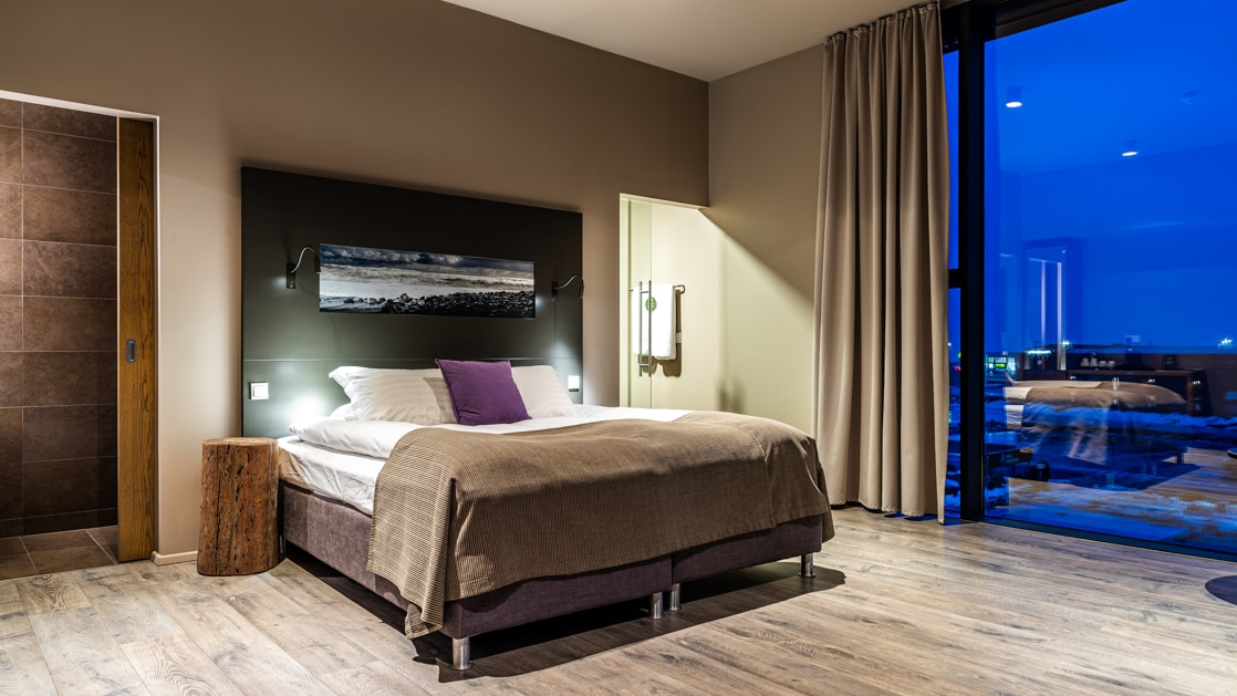 Deluxe room at Hotel Vik i Myrdal with king-size bed, floor-to-ceiling windows, wooden floor & contemporary feel.