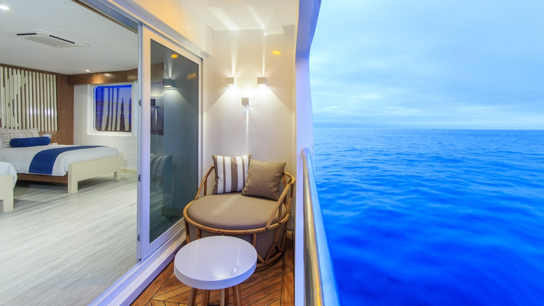 View from private balcony looking into a Golden Suite aboard the Elite catamaran in Galapagos. Balcony has a rattan chair & small coffee table.