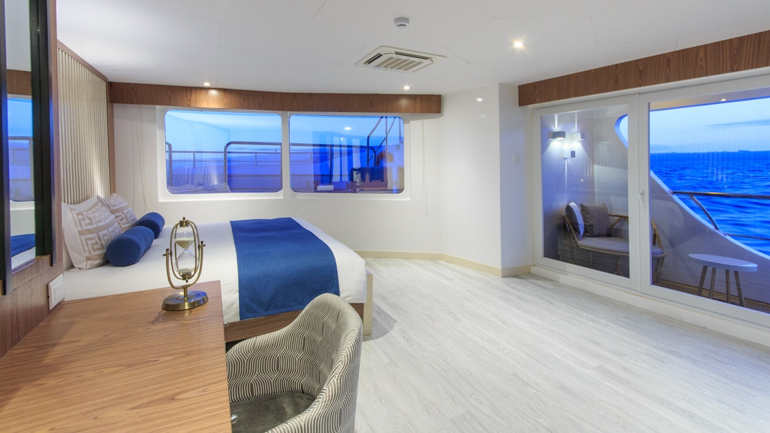 Panoramic suite aboard the Elite catamaran in Galapagos, with double bed, desk, sliding glass door to private balcony & many windows.