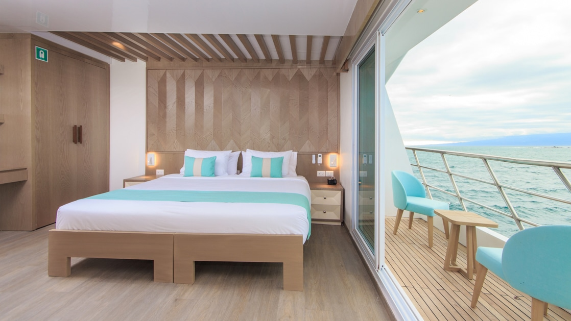 Double bed with white, beige & teal bedding in room with white & wood accents & glass wall with door onto private balcony on M/C Endemic.