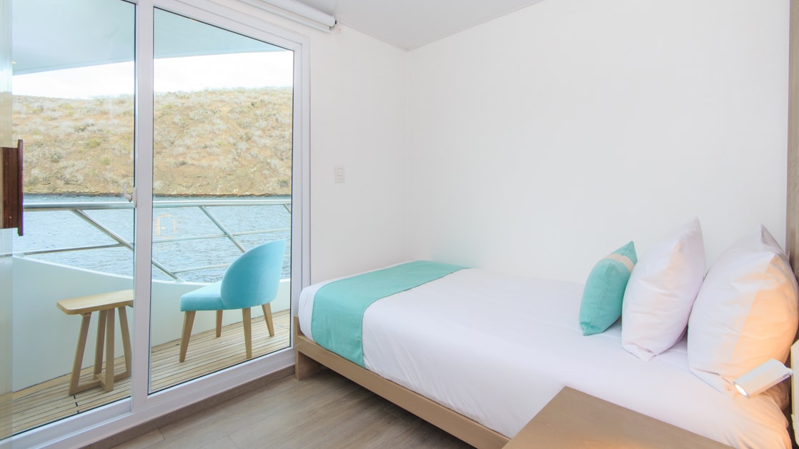 Twin bed with white, beige & teal bedding in slender room with white & wood accents & view onto glass sliding door & private balcony.