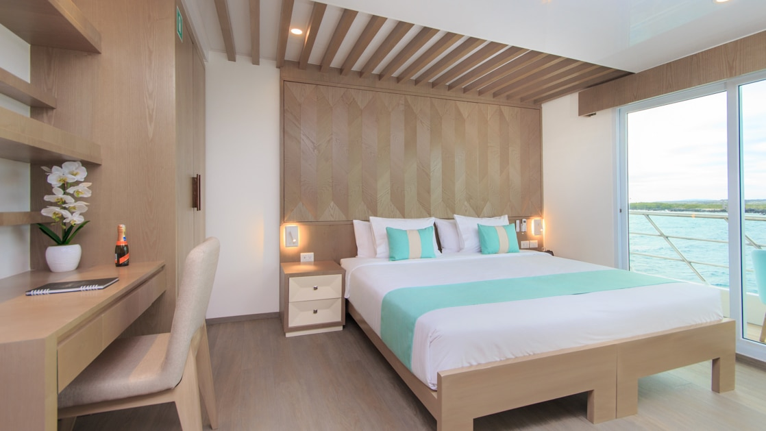 Double bed with white, beige & teal bedding in room with white & wood accents, wooden desk & shelves & glass door onto private balcony.