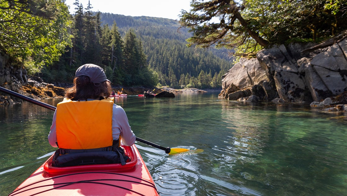 View from behind woman paddling a red kayak in calm waters among rocky tree-lined shore in Alaska.